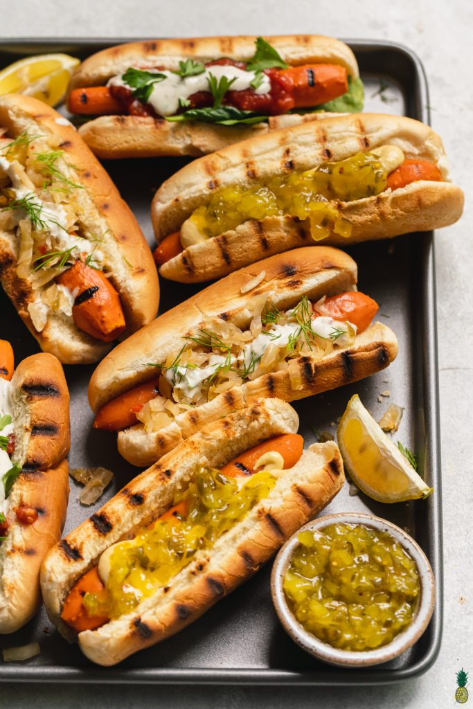 close up shot of loaded vegan carrot hot dogs on a sheet pan with lemon and relish by sweet simple vegan