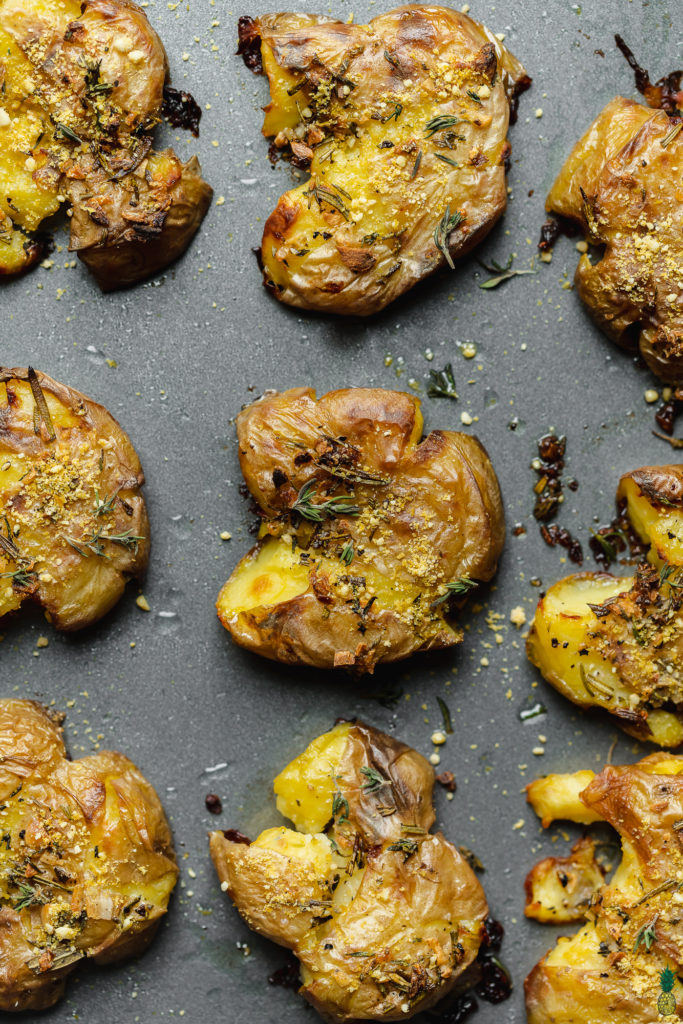 close up shot of garlic and herb smashed potatoes on a baking sheet