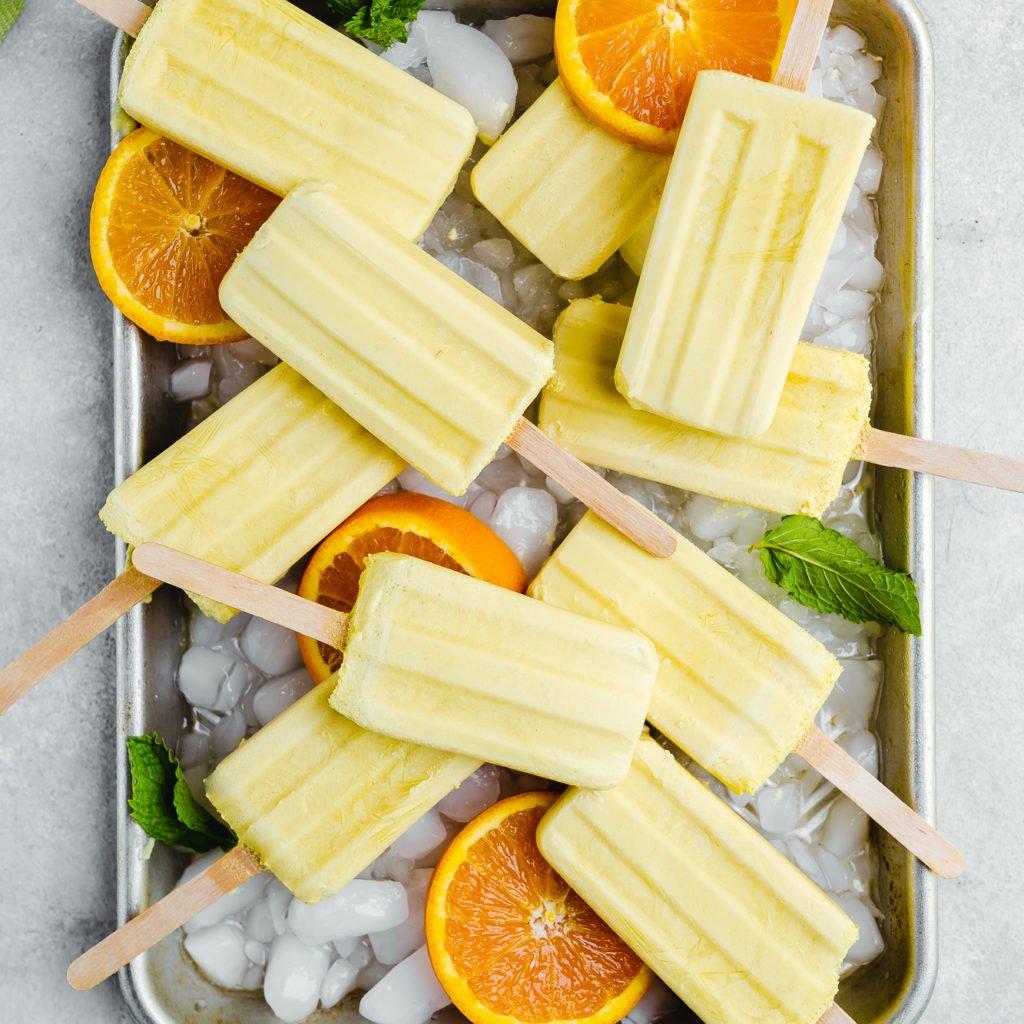 5 ingredient vegan orange creamsicle popsicles on a tray by sweet simple vegan