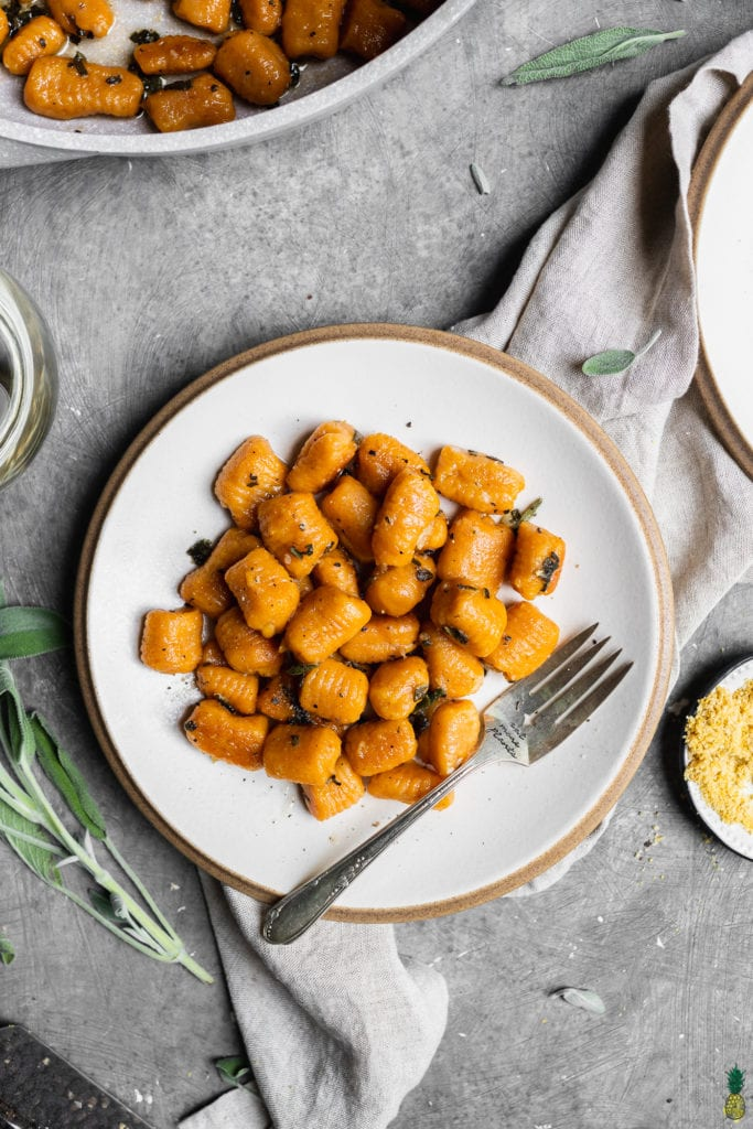 Vegan pumpkin gnocchi with sage butter sauce on a white plate with a fork and vegan parmesan cheese