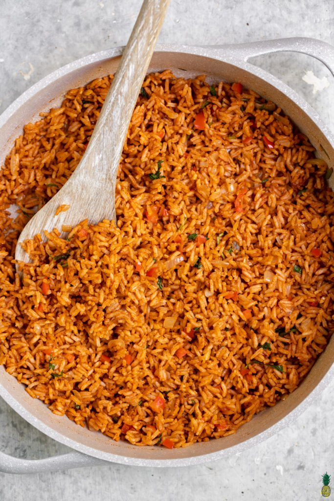 Close up shot of Spanish Rice in a white pan with a serving spoon