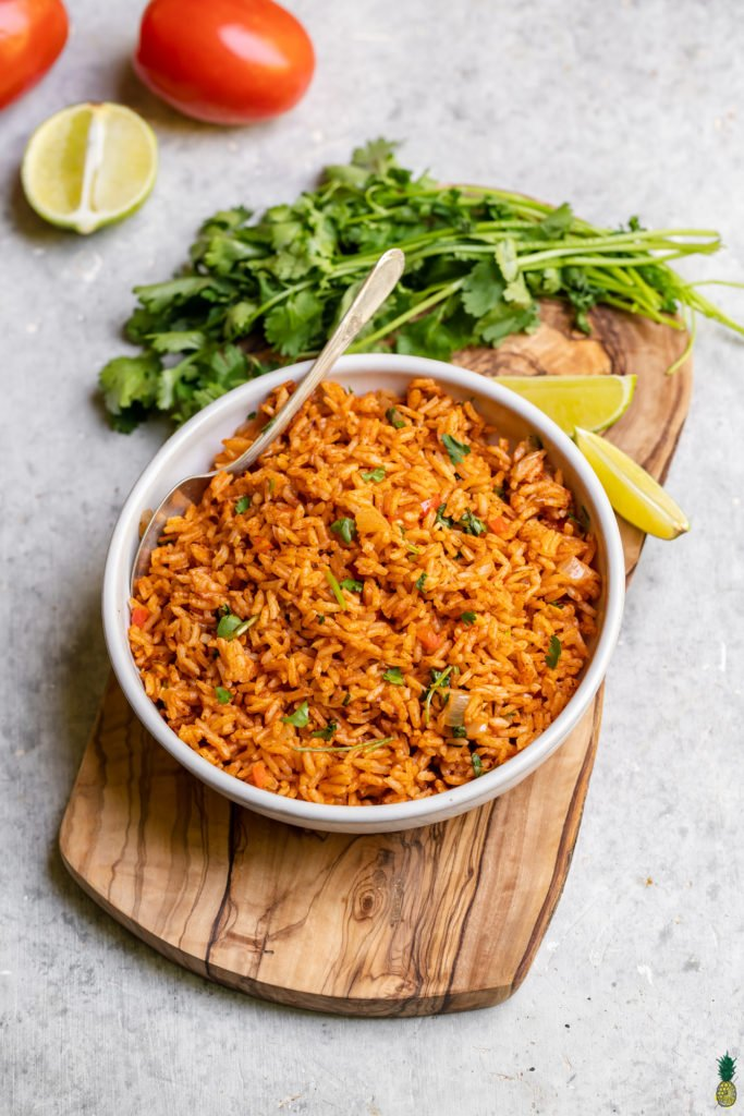 Homemade Spanish Rice in a white bowl with a serving spoon