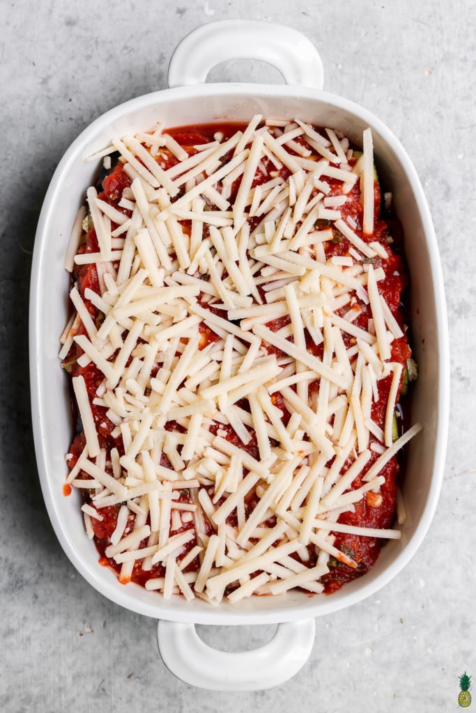 overhead image of eggplant rollatini in a baking dish with cheese and sauce uncooked
