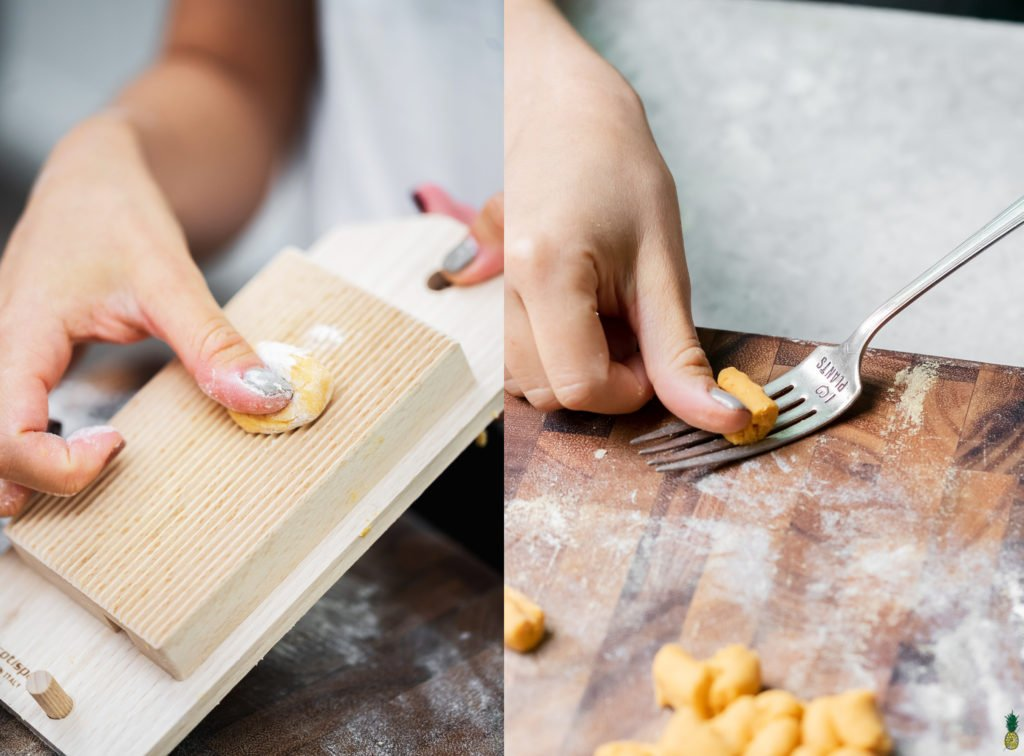 Rolling the gnocchi on a gnocchi board and using a fork.