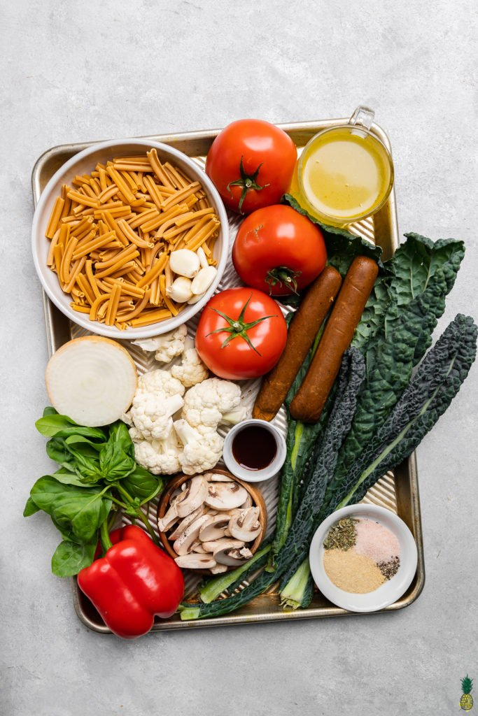 Fresh ingredients on a sheet pan to make an easy vegan sheet pan pasta recipe by sweet simple vegan