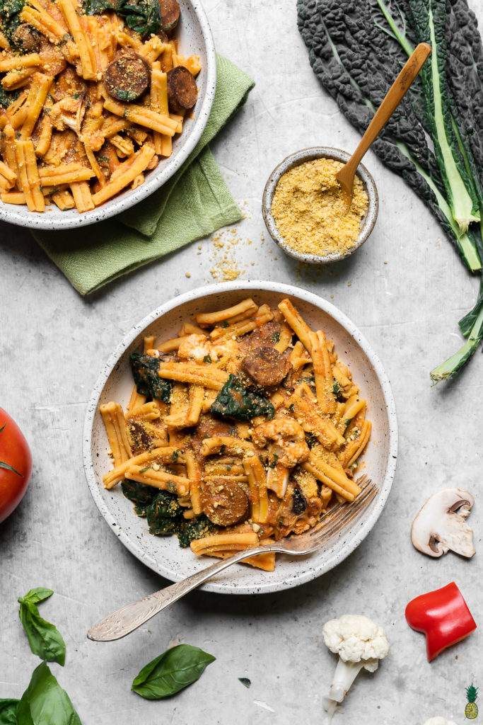 Gluten free pasta with roasted red pepper and tomato sauce in a ceramic bowl; food photograph by sweet simple vegan
