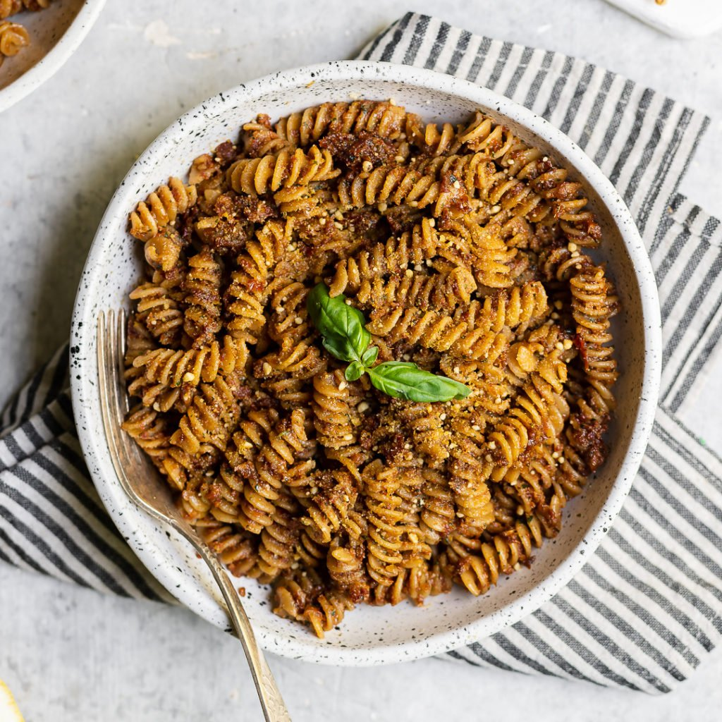 Bowl of vegan sun dried tomato pesto pasta with a towel food photography