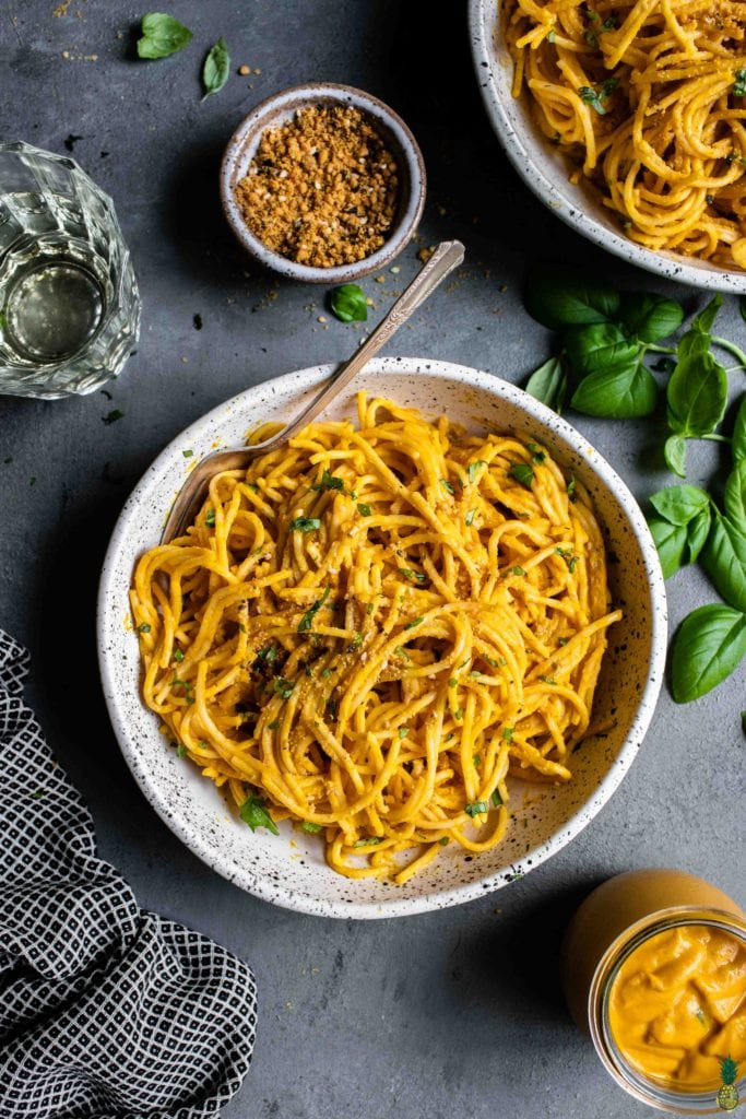 a white bowl of creamy vegan squash pasta with parmesan and white wine by sweet simple vegan