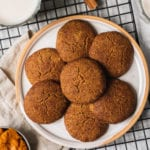 vegan gluten free pumpkin snickerdoodles on a plate with a cooling rack and almond milk