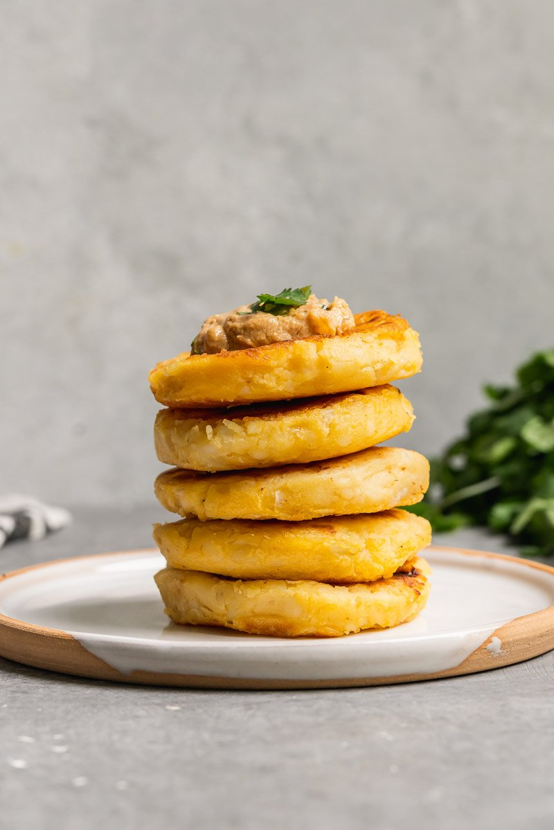 a stack of vegan llapingachos on a white plate