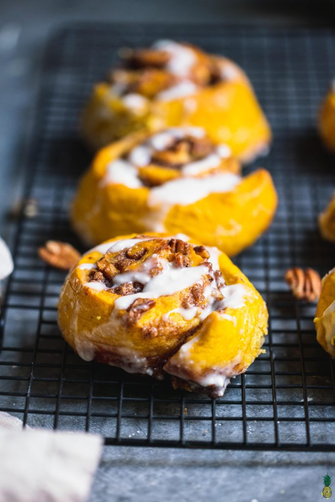Close up shot of vegan pumpkin cinnamon rolls on a cooling rack with cream cheese icing drizzle by sweet simple vegan