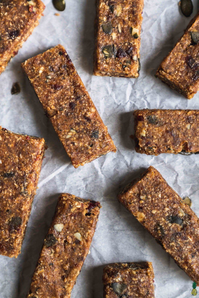 no bake peanut butter breakfast bars on parchment paper with flowers by sweet simple vegan