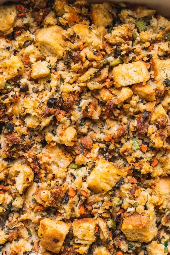 Closeup shot of a buttermilk biscuit thanjsgiving stuffing with vegetables and herbs by sweetsimplevegan