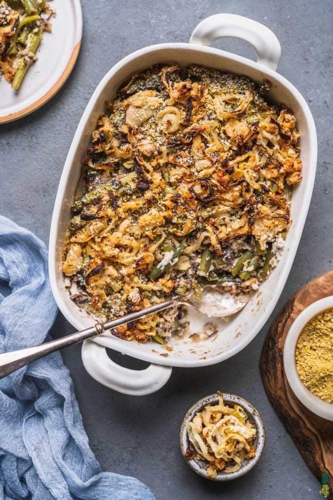an overhead shot of a vegan green bean casserole with oven baked onions and vegan parmesan cheese