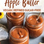 three jars filled with homemade apple butter surrounded by flowers apples and lemon by sweet simple vegan for pinterest