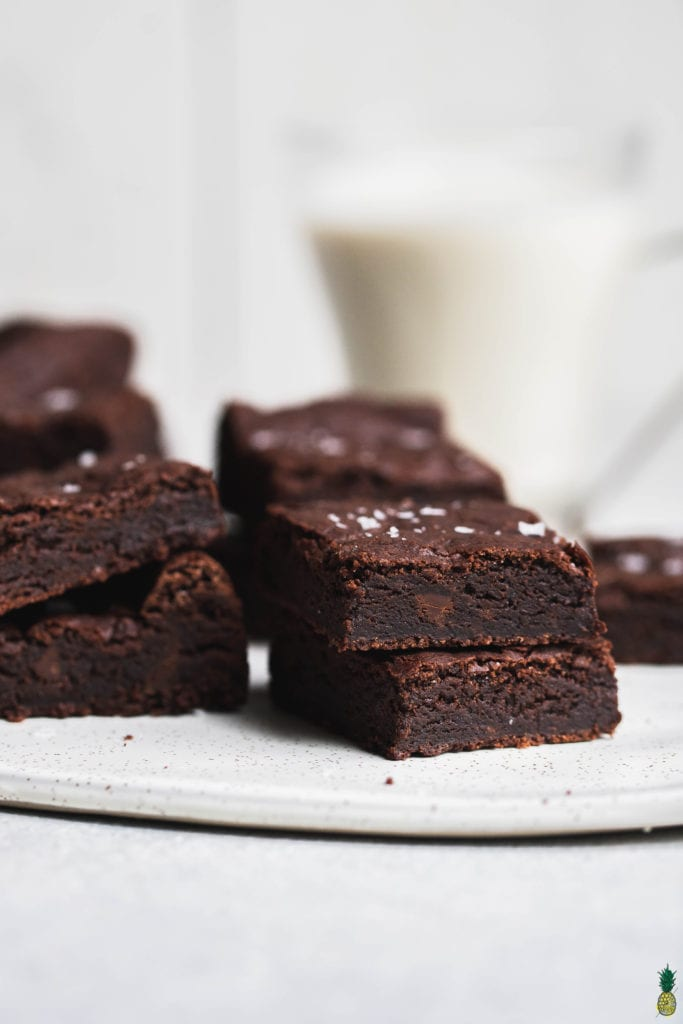 vegan brownies sprinkled with maldon salt and stacked up on a marble platter with almond milk in the back by sweet simple vegan