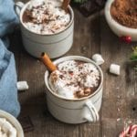 cups of vegan hot cocoa on a wooden board with whipped cream, peppermint and cinnamon sticks by sweet simple vegan