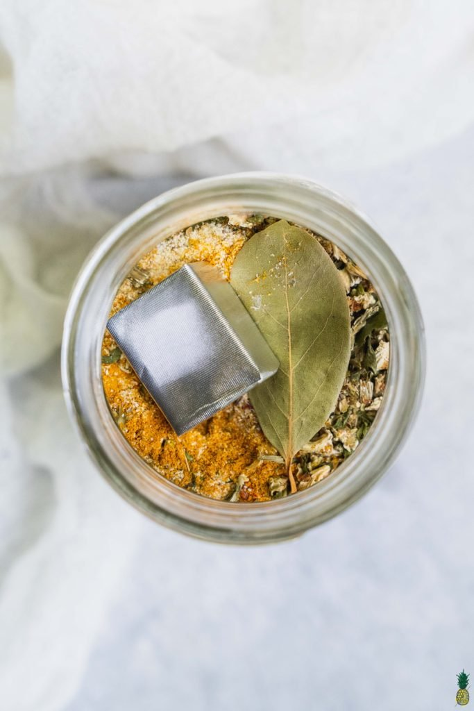 Overhead shot of a lentil and split pea soup mix in a jar with a bay leaf and bouillon cub by sweet simple vegan