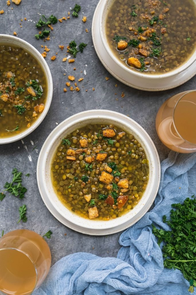 An overhead shot of a vegan lentil and split pea soup in a white bowl on a dark background by sweet simple vegan