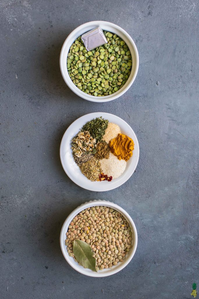 Ingredients to make lentil and split pea soup in small white bowls on a dark gray board by sweet simple vegan