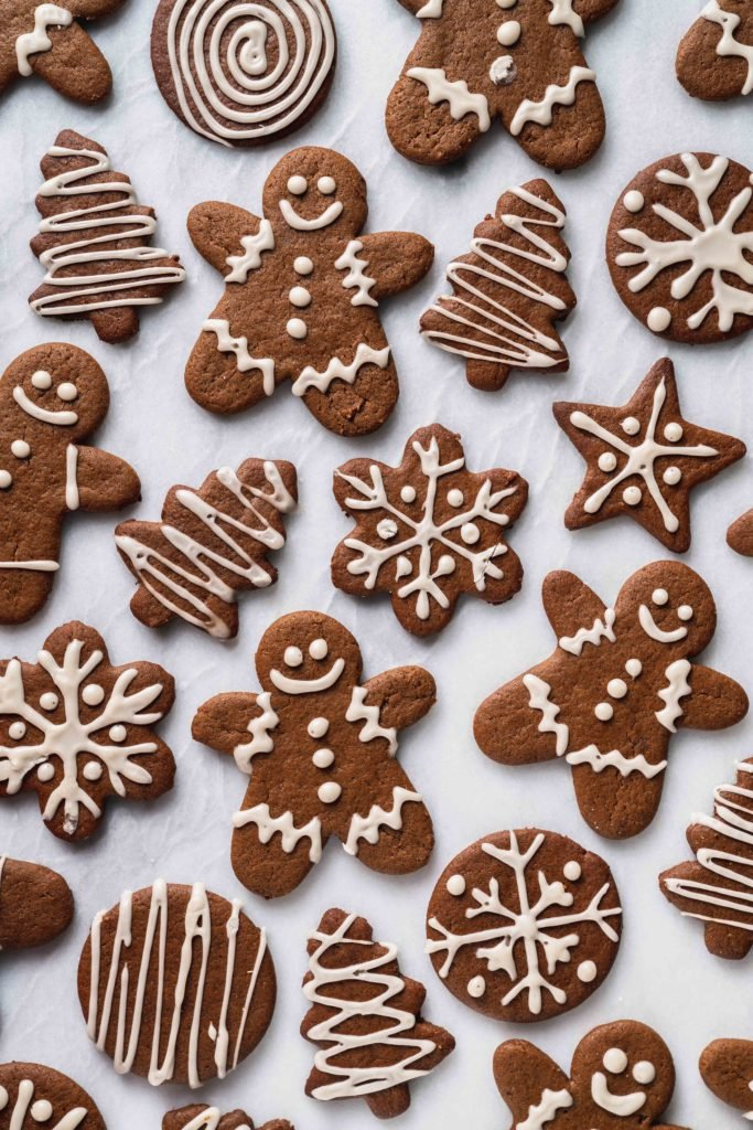 An overhead shot of iced vegan gingerbread cookies on a white marble board