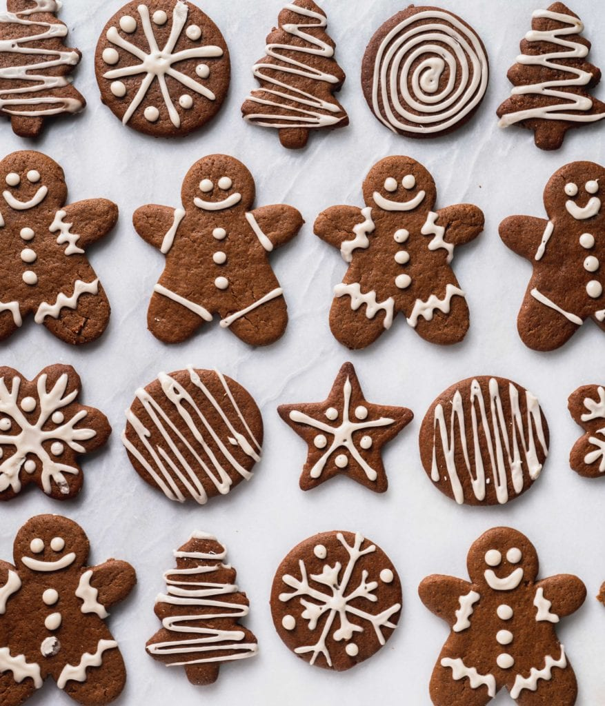 an overhead shot of gingerbread cookies with white icing on a marble background