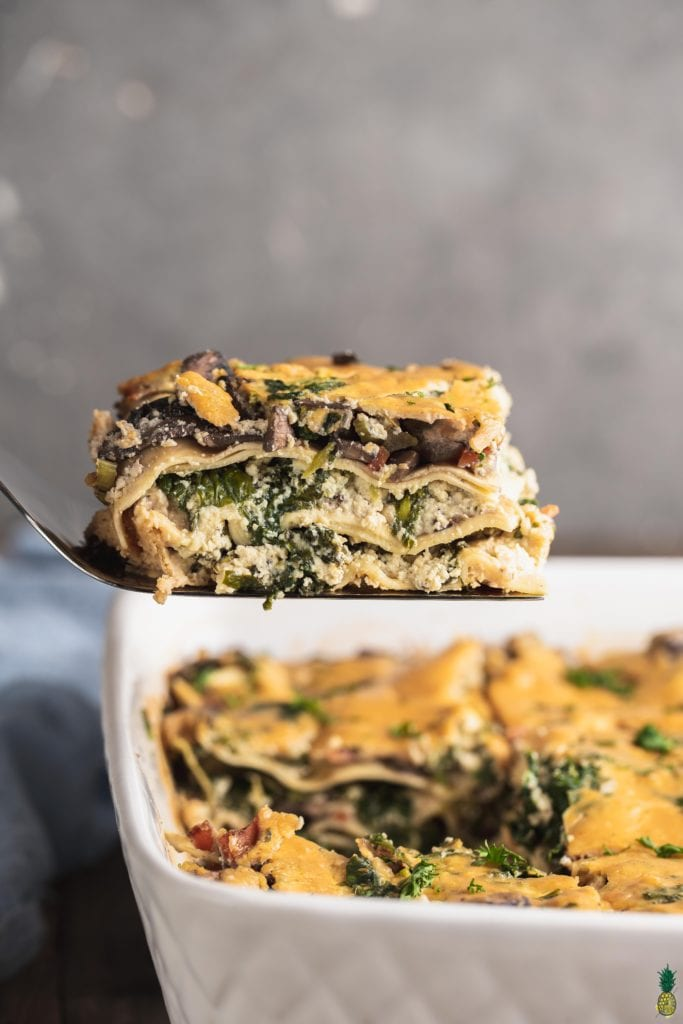 A cut slice of vegan white lasagna on a spatula being scooped out of the dish by sweet simple vegan