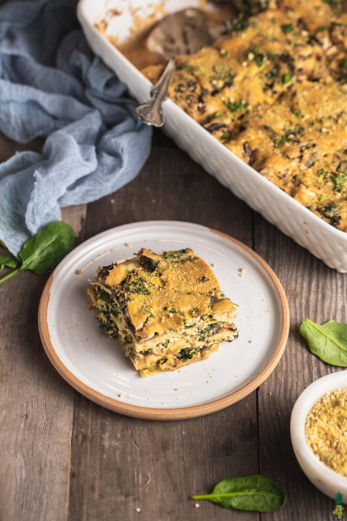 a slice of vegan white lasagna next to a white baking dish with vegan parmesan cheese by sweet simple vegan