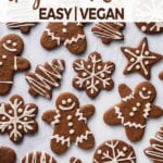 An overhead shot of iced vegan gingerbread cookies on a white marble board for pinterest