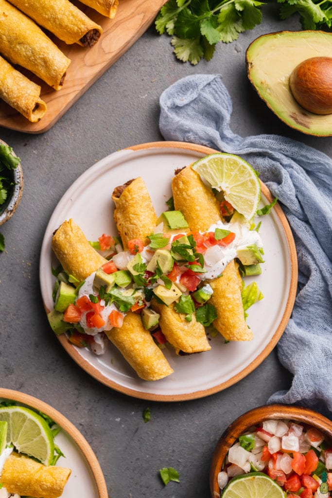 a plate of mushroom potato taquitos with vegan sour cream, pico de gallo, avocado and lime