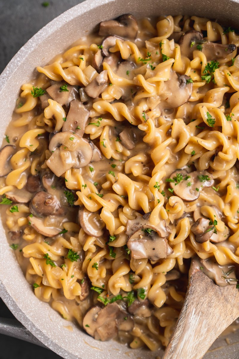 overhead close up image of mushroom stroganoff with wooden spoon
