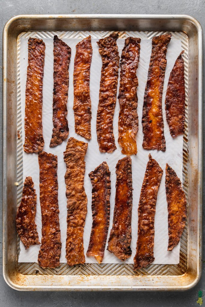 baked crispy vegan rice paper bacon on a baking sheet by sweet simple vegan