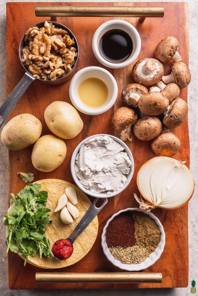 A photo of ingredients needed to make mushroom potato taquitos on a wooden board