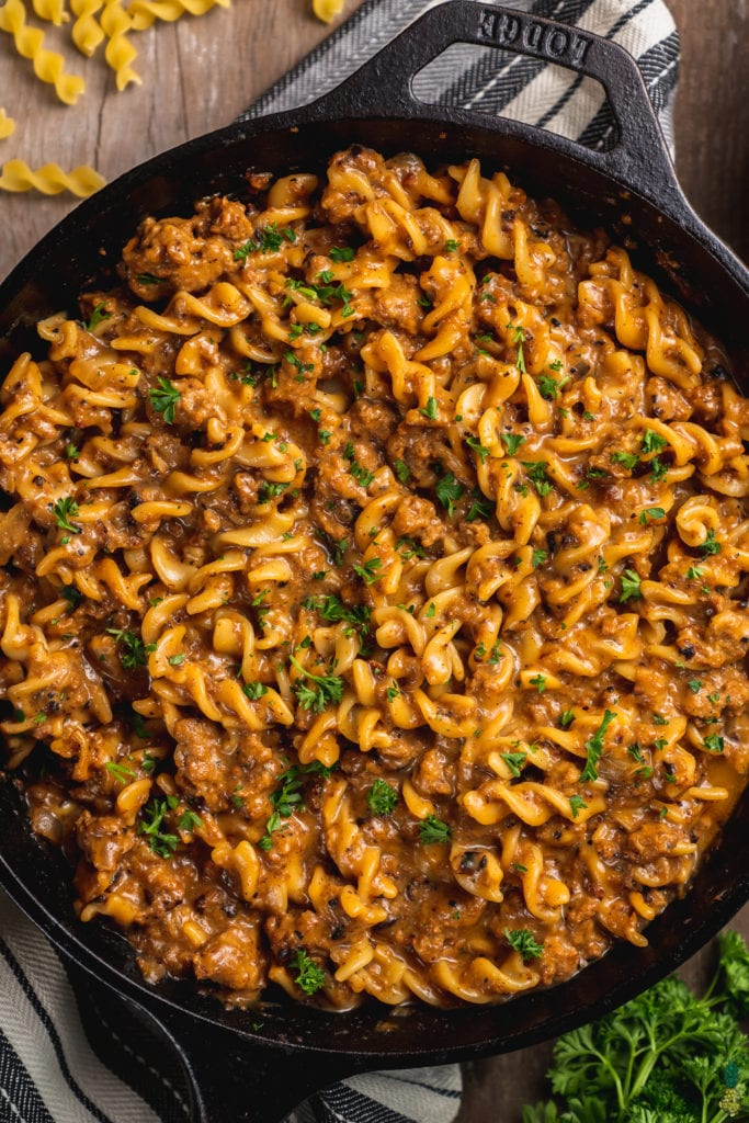 A close up shot of homemade hamburger helper in a cast iron skillet on a wooden backdrop with parsley on top by sweet simple vegan
