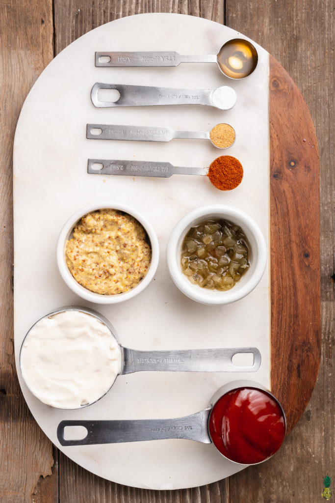 Ingredients needed to make vegan big mac sauce in small containers on a marble board by sweet simple vegan