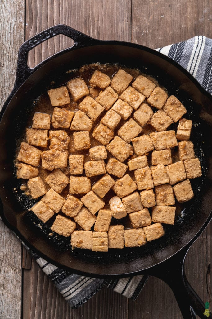 Over head image of uncooked sesame ginger tofu in cast iron skillet.