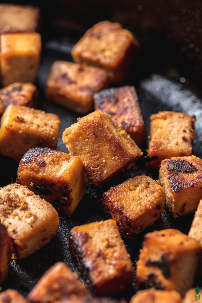 macro image of sesame ginger tofu cubes in cast iron skillet shot at 3/4 angle.