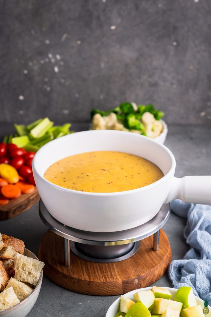 vegan cheese fondue in a white pot surrounded by dippers by sweet simple vegan