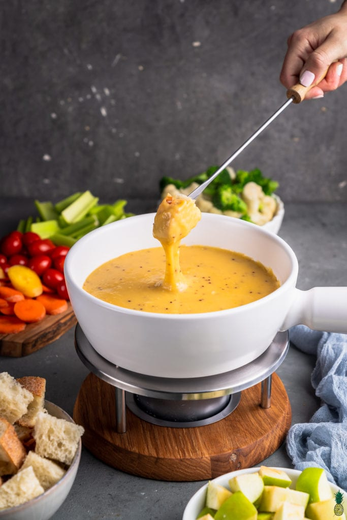 A photo of bread being dipped into vegan cheese fondue in a white pot surrounded by dippers by sweet simple vegan
