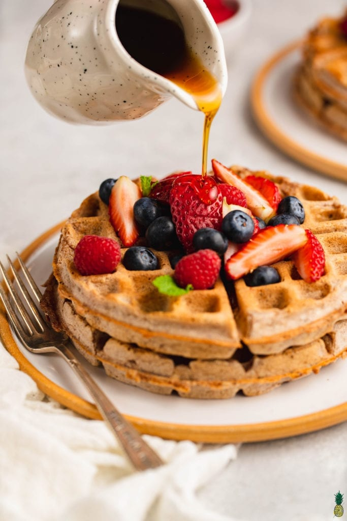 macro image of rye waffles topped with fruit and maple syrup being poured over.