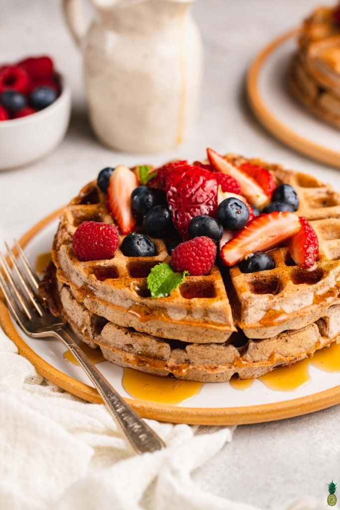 Macro image of vegan rye waffles topped with fruit and smothered with maple syrup.