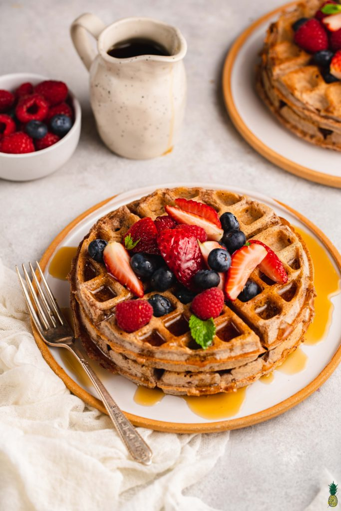 three-quarter angle of rye waffles topped with fruit and maple syrup.