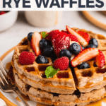 Macro image of vegan rye waffles topped with fruit and smothered with maple syrup for pinterest
