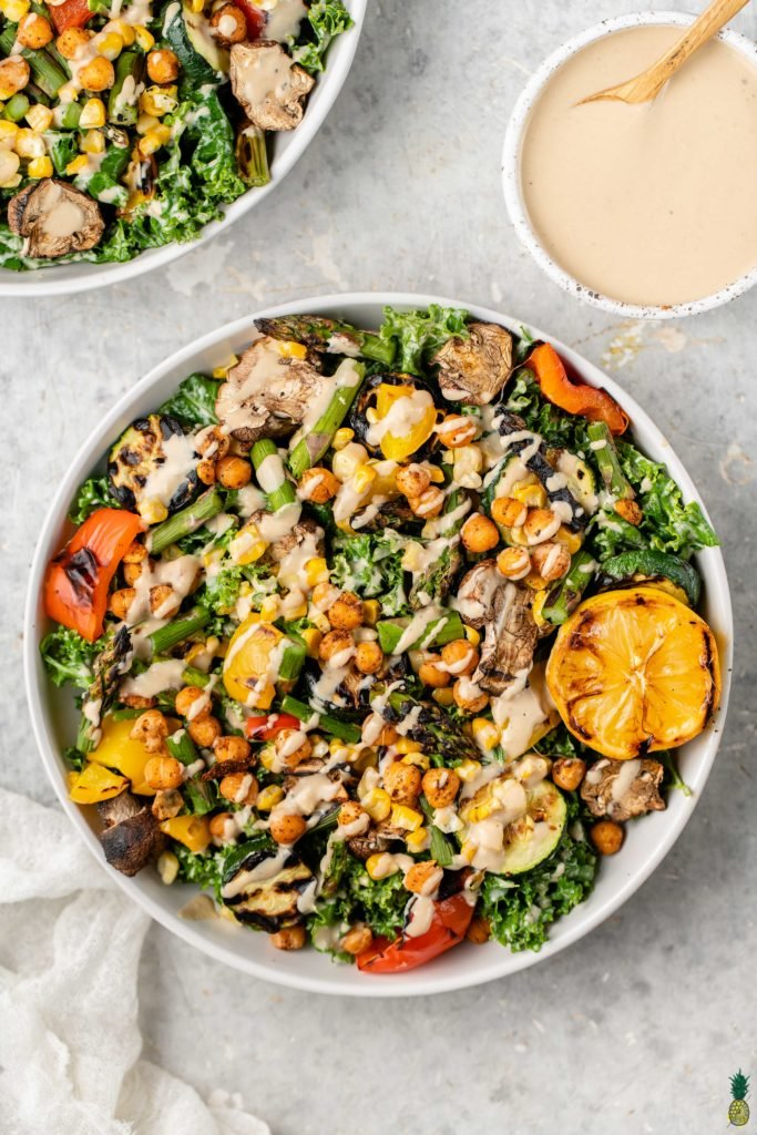 Tahini dressing on a roasted vegetable and chickpea salad in a white bowl by sweet simple vegan