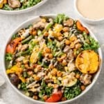 A grilled vegetable salad with spiced chickpeas and tahini dressing in a white bowl with a lemon half by sweetsimplevegan