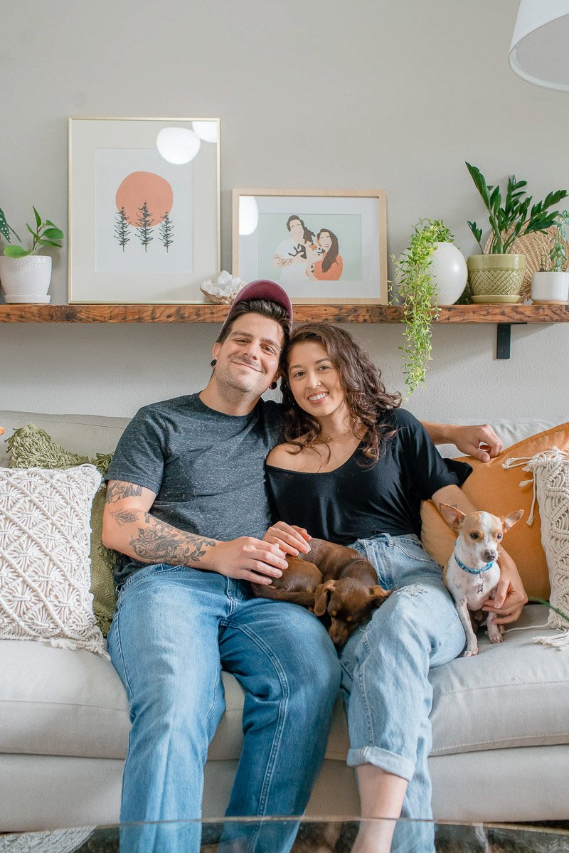 Chris and Jasmine sitting on couch with the dogs