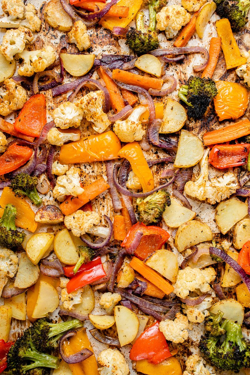 a close up of roasted vegetables on a silver baking sheet with a blue towel