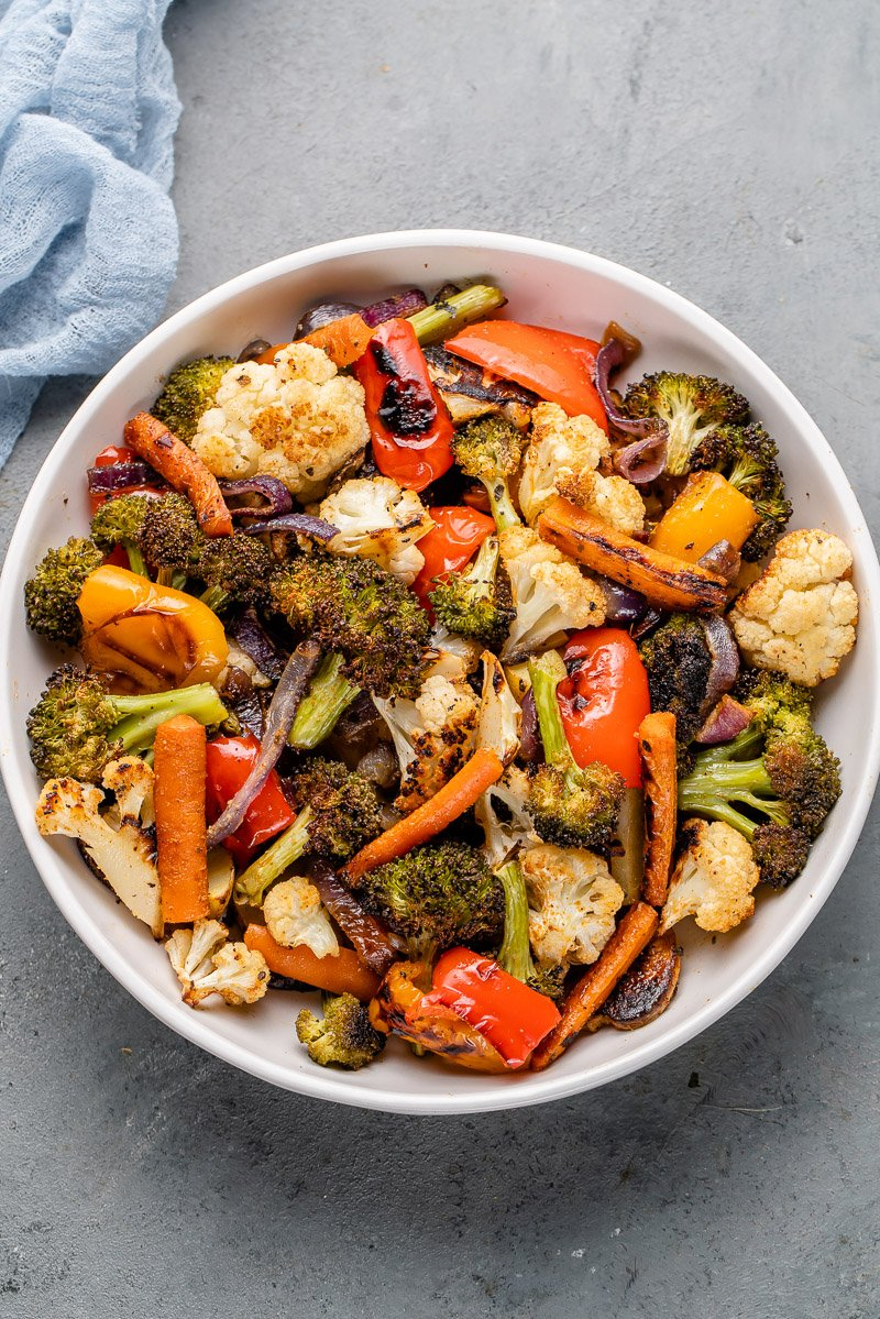roasted vegetables in a white bowl with a blue towel