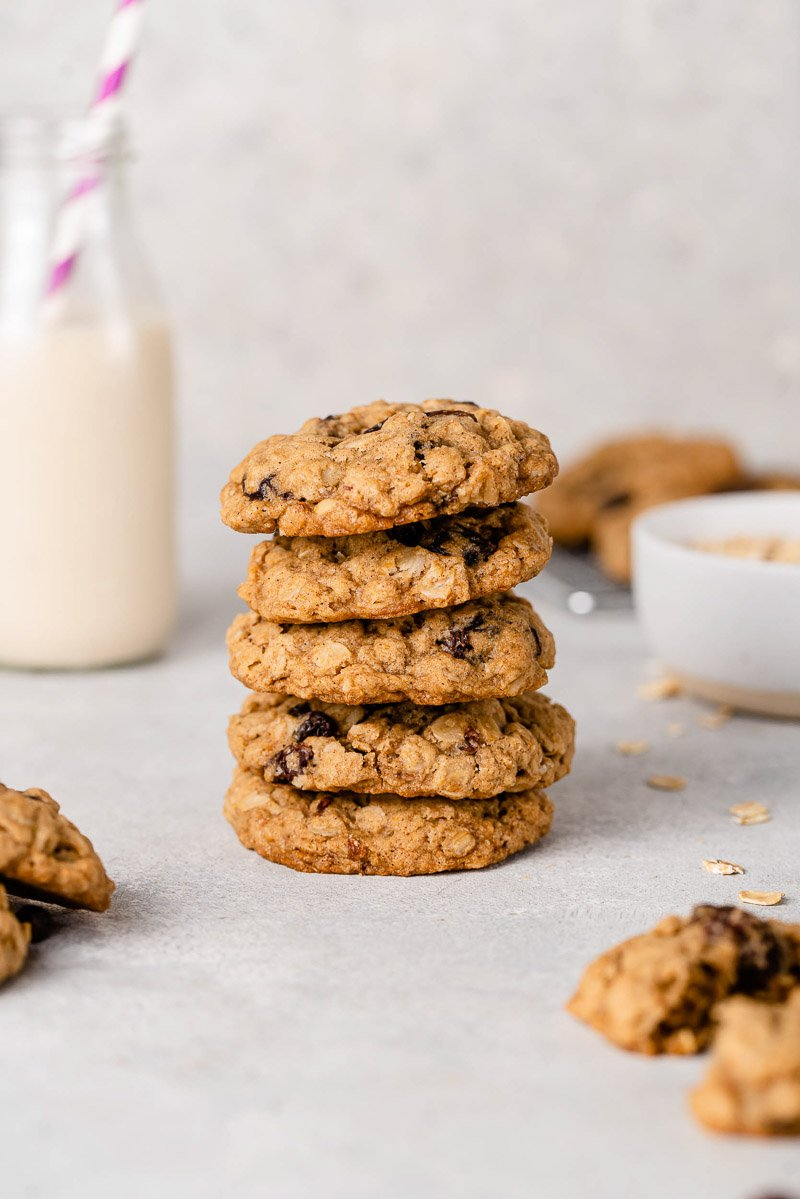 vegan oatmeal raisin cookies in a tall stack with a glass of oat milk by sweet simple vegan