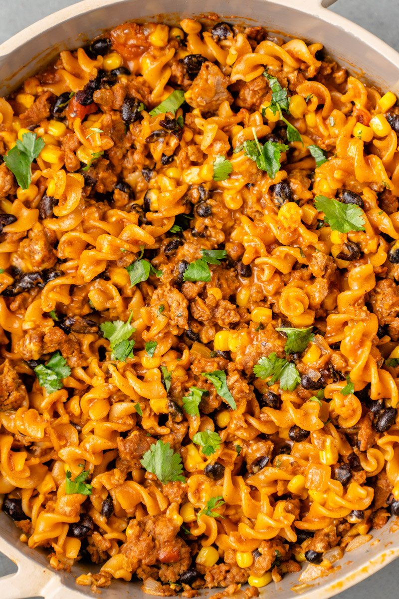 close up shot of creamy vegan taco pasta in a beige pan with cilantro on top by sweet simple vegan